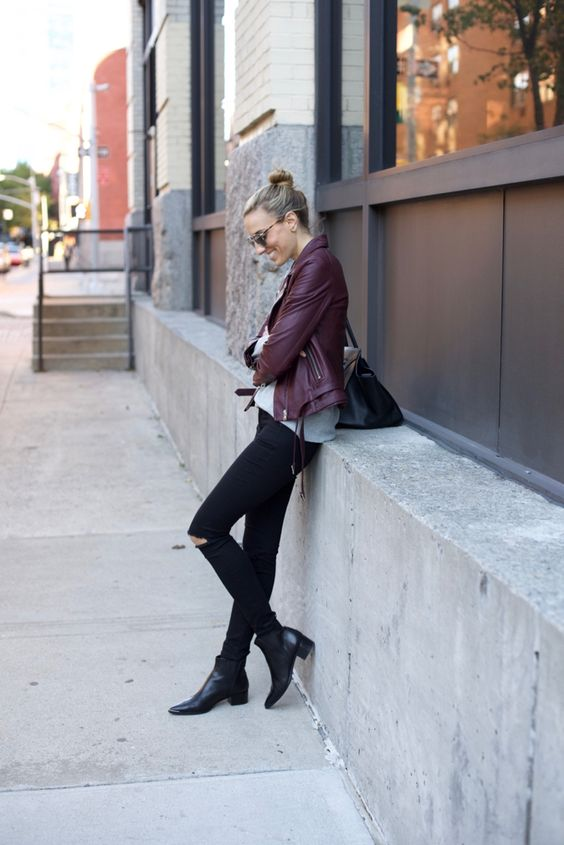 women's outfit with a burgundy biker jacket and ripped jeans