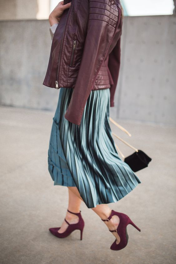woman wearing a burgundy racer jacket  with a pleated skirt