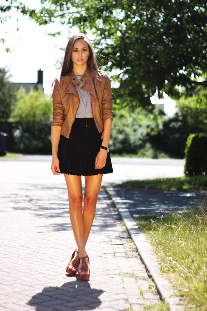 girl wearing a short black skirt and a brown cropped leather jacket
