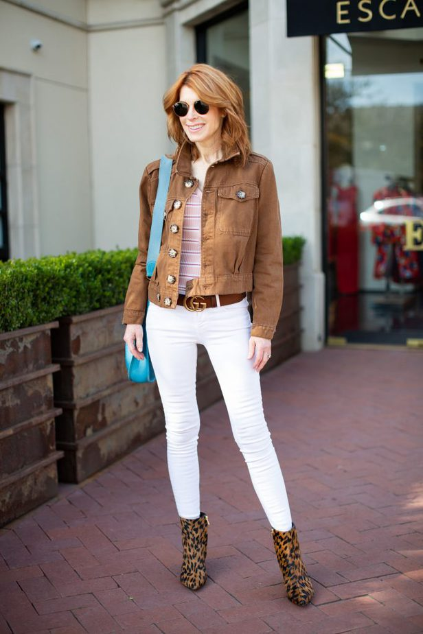 A casual look with a brown denim jacket and white jeans.