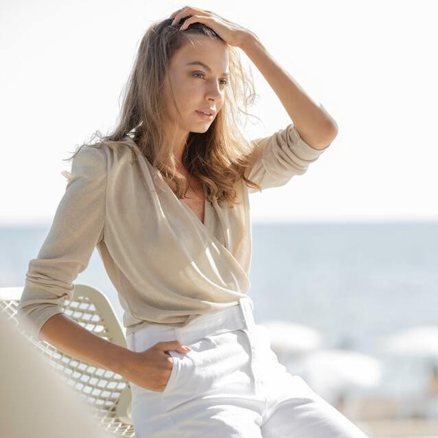 woman wearing a beige top with white jeans