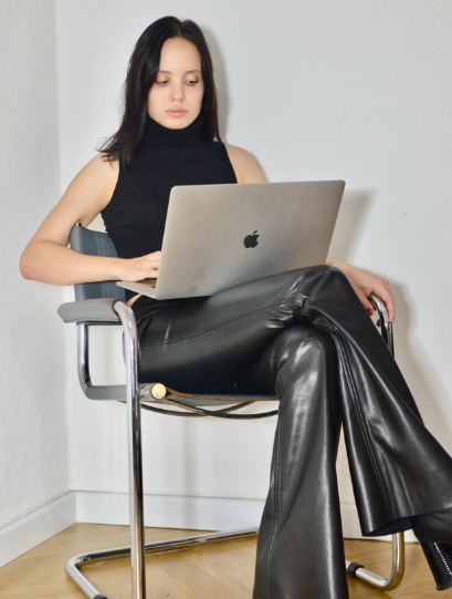 woman sitting on chair wearing a sleeveless top and flared faux leather pants