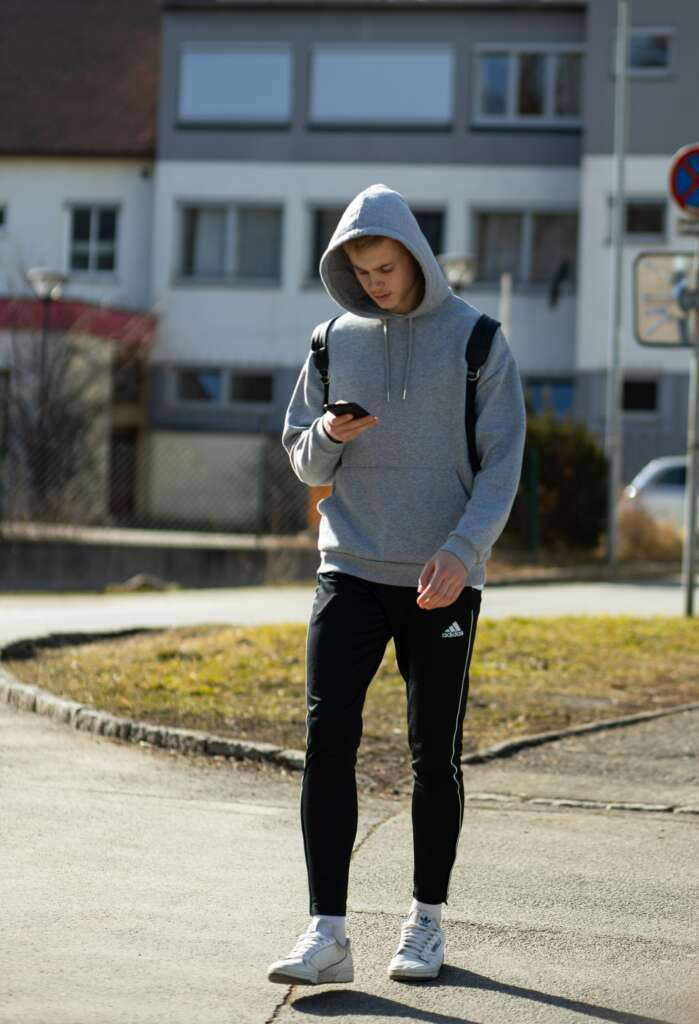 man wearing a grey hoodie and track pants