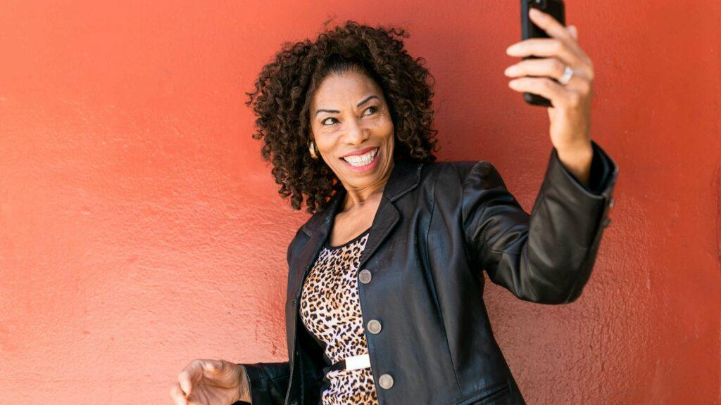 mature stylish woman wearing a black leather jacket with leopard print dress