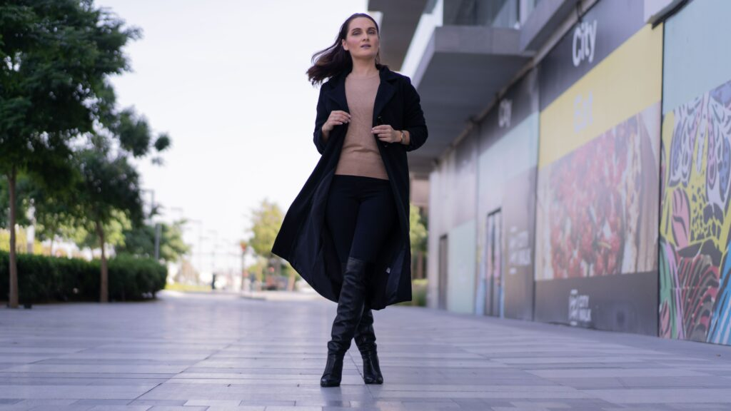 woman wearing a sweater and black jeans with long boots and a trench coat