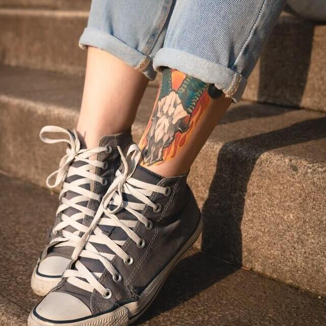 woman with tatoo wearing jeans with high tops