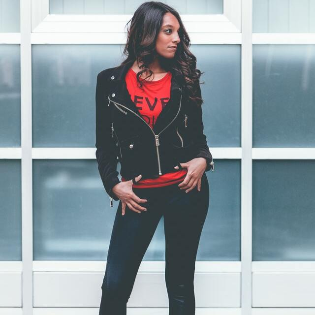 woman wearing cropped biker jacket and red top with black jeans
