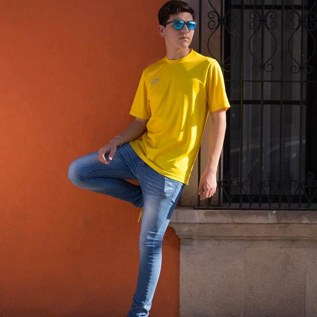 man in blue skinny jeans and yellow t-shirt