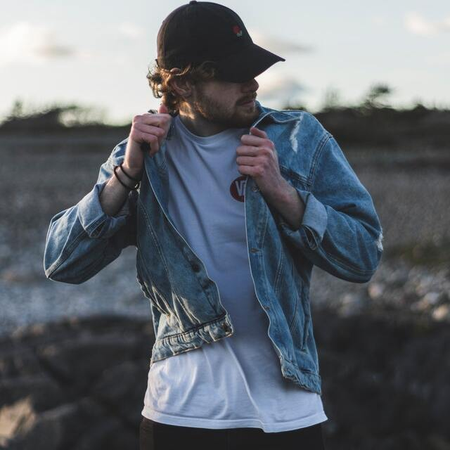 men's outfit: white t-shirt, jeans, and a denim jacket with snapback.