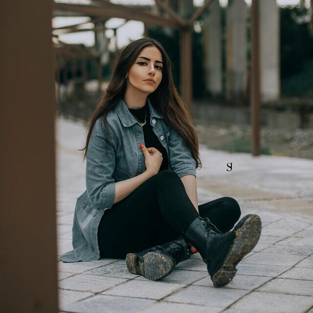 woman wearing a lightweight denim jacket and black jeans.