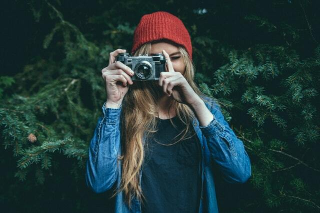 girl with a camera wearing a denim jacket and beanie