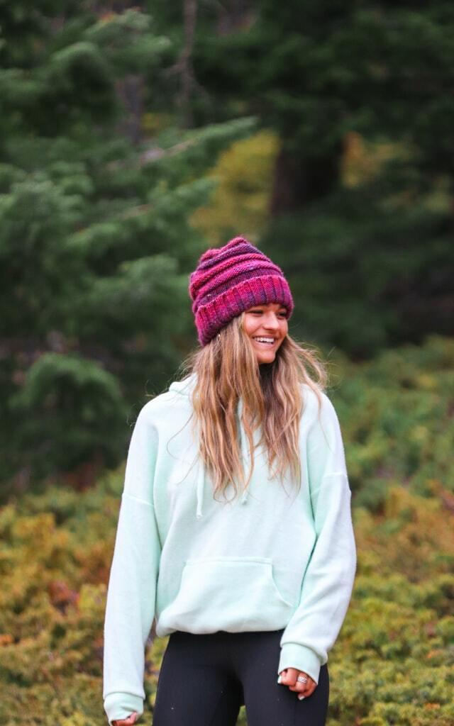 Girl wearing a white sweatshirt and pink  beanie
